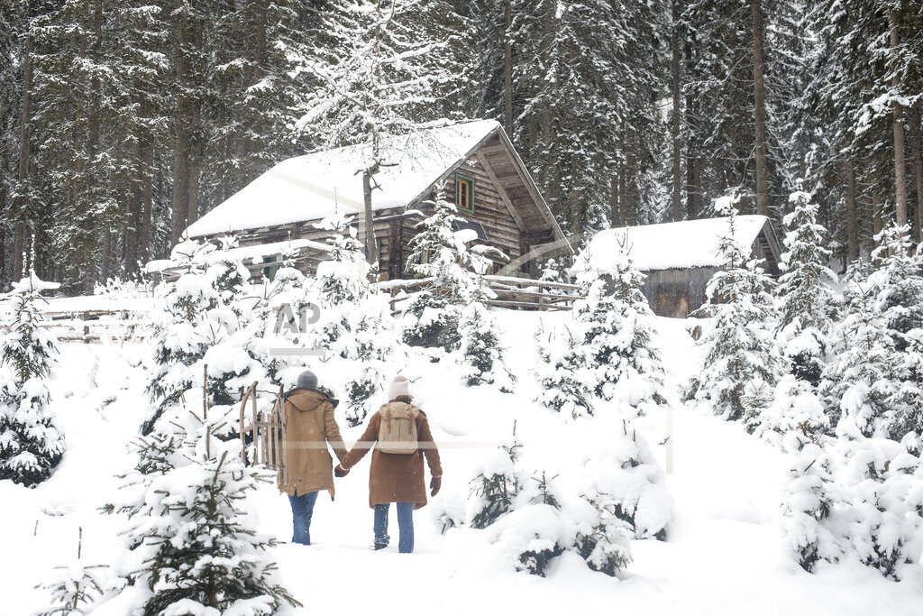 Young couple holding hands while walking on snow