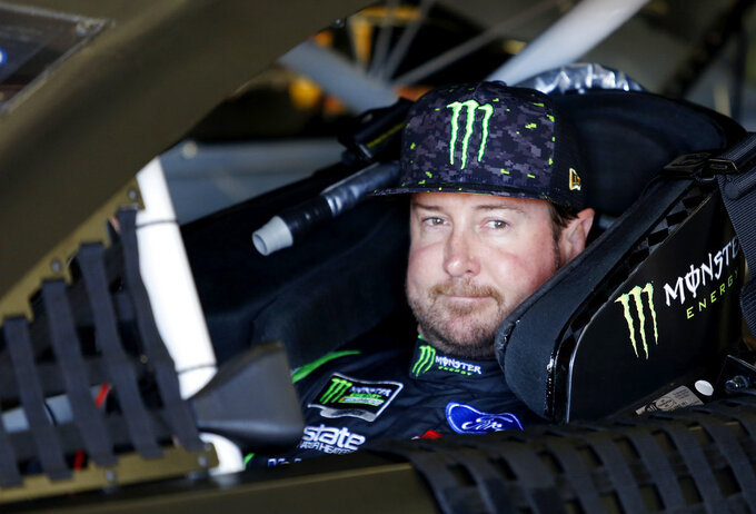 FILE - In this July 20, 2018, file photo, Kurt Busch waits in his car before NASCAR Cup Series auto racing practice at New Hampshire Motor Speedway in Loudon, N.H. NASCAR's driver carousel will spin long after the season finale. Former Cup champions Busch and Matt Kenseth, and Daniel Suarez, AJ Allmendinger, Regan Smith and Jamie McMurray are among the drivers certain to start next season with new teams or new roles. (AP Photo/Mary Schwalm, File)