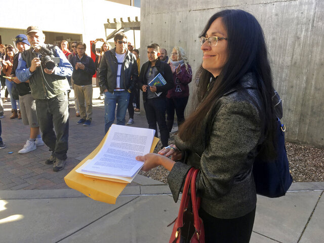 FILE - In this Nov. 18, 2016, file photo, University of New Mexico Chicana and Chicano Studies Department Chair Irene Vasquez holds a letter with hundreds of signatures, asking then-school president Bob Frank to declare the campus a