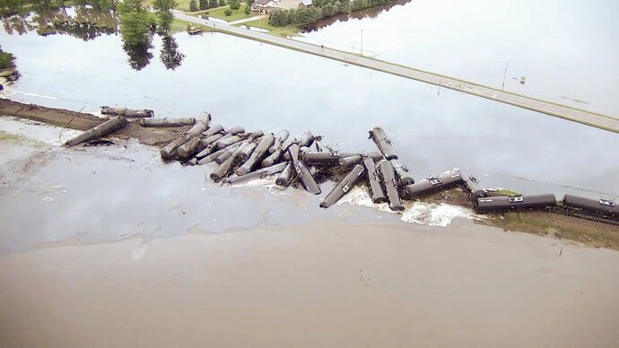 FILE - In this Friday, June 22, 2018, file aerial drone image taken from video and provided by the Sioux County Sheriff's Office, tanker cars carrying crude oil are shown derailed about a mile south of Doon, Iowa. BNSF Railway acknowledged Friday, Aug. 10, 2018, that flooding played a role in a derailment that loosed thousands of gallons of oil into northwest Iowa floodwaters. The National Transportation Safety Board report cited heavy rainfall in the area 48 hours before the derailment. (Sioux County Sheriff's Office via AP, File)