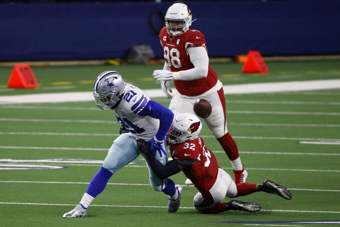 Dallas Cowboys running back Ezekiel Elliott (21) has the ball stripped away by Arizona Cardinals safety Budda Baker (32) as defensive tackle Corey Peters (98) looks on in the first half of an NFL football game in Arlington, Texas, Monday, Oct. 19, 2020. (AP Photo/Ron Jenkins)
