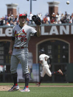 St. Louis Cardinals pitcher Jack Flaherty, left, waits for a new ball after allowing a solo home run to San Francisco Giants' Evan Longoria, rear, during the seventh inning of a baseball game in San Francisco, Sunday, July 7, 2019. (AP Photo/Jeff Chiu)
