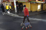 A woman wearing a mask to curb the spread of the new coronavirus walks her dog outside the Haiti market in La Paz, Bolivia, Tuesday, June 23, 2020. Health authorities say that a butcher at the marker died several weeks ago of COVID related symptoms, prompting its closure. (AP Photo/Juan Karita)
