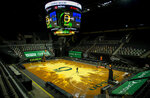 A worker crosses the court after the NCAA college basketball game between Oregon and UCLA cancelled, Wednesday, Dec. 23, 2020, at Matthew Knight Arena in Eugene, Ore. (AP Photo/Andy Nelson)