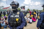A police officer stands guard as protesters sit down during the Good Trouble Tuesday march for Breonna Taylor, Tuesday, Aug. 25, 2020, in Louisville, Ky. (Amy Harris/Invision/AP)d
