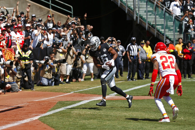 Oakland Raiders wide receiver Tyrell Williams (16) scores a touchdown as Kansas City Chiefs free safety Juan Thornhill (22) looks on during the first half of an NFL football game Sunday, Sept. 15, 2019, in Oakland, Calif. (AP Photo/D. Ross Cameron)