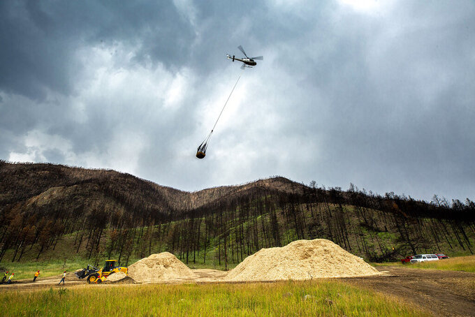 In this Friday, Aug. 6, 2021 photo, a helicopter picks up mulch to spread in Poudre Canyon, about 50 miles west of Fort Collins, to try to stem silt runoff during large rains near Red Feather Lakes, Colo. (Kevin J. Beaty/Colorado Public Radio via AP)