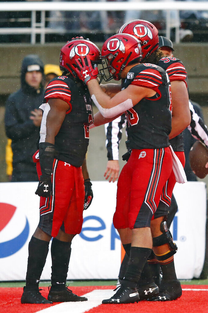 Utah running back Zack Moss, left, celebrates with teammates after his 1-yard touchdown run during the first half of an NCAA college football game against Arizona State on Saturday, Oct. 19, 2019, in Salt Lake City. (AP Photo/Rick Bowmer)