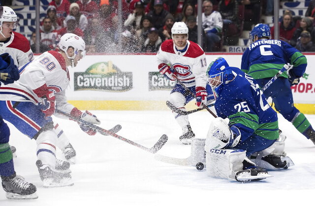 Vancouver Canucks goalie Jacob Markstrom (25), of Sweden, stops Montreal Canadiens' Tomas Tatar (90), of Slovakia, during the first period of an NHL hockey game in Vancouver, British Columbia, Tuesday Dec. 17, 2019. (Darryl Dyck/The Canadian Press via AP)