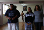 In this June 6, 2019 photo, Carlos Suarez's parents, Rafael Suarez Reyes, left, and Alejandra Benhumea Gutierrez, right, along with his cousin Ana Paola Suarez, watch as he practices his bodybuilding poses as part of his daily training regimen ahead of the Pan Am Games, at the neighborhood gym owned by his parents in Toluca, Mexico. Suarez and female fitness competitor Xyomara Valdivia will become the first Mexicans to represent their country in bodybuilding at the Pan Am Games, with this year marking the first time the discipline has been included as an official sport(AP Photo/Rebecca Blackwell)