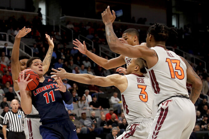 Liberty guard Georgie Pacheco-Ortiz (11) tries to pass under pressure from several Virginia Tech players during the first half of a second-round game in the NCAA men's college basketball tournament Sunday, March 24, 2019, in San Jose, Calif. (AP Photo/Jeff Chiu)