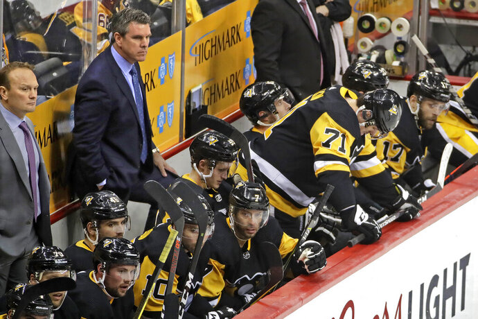 Pittsburgh Penguins coach Mike Sullivan, rear second from left, and assistant Sergei Gonchar, left, stand behind their bench as Evgeni Malkin (71) waits to take the ice, during the third period in Game 4 of an NHL hockey first-round playoff series against the New York Islanders in Pittsburgh, Tuesday, April 16, 2019. The Islanders won 3-1, sweeping the series. (AP Photo/Gene J. Puskar)