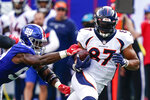 Denver Broncos tight end Noah Fant (87) protects the ball from New York Giants' Lorenzo Carter (59) during the first half of an NFL football game Sunday, Sept. 12, 2021, in East Rutherford, N.J. (AP Photo/Matt Rourke)