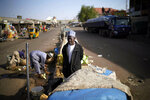 A Nigerian salesman stands in the middle of the normally busy street outside the central market in Kaduna, Nigeria, Saturday Feb. 16, 2019. Nigeria's electoral commission delayed the presidential election until Feb. 23, making the announcement a mere five hours before polls were set to open Saturday. (AP Photo/Jerome Delay)