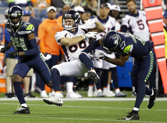 FILE - In this Aug. 8, 2019, file photo, Seattle Seahawks' Marquise Blair, right, hits Denver Broncos wide receiver Nick Williams, center, drawing a penalty flag for unnecessary roughness, as Seahawks defensive back Simeon Thomas, left, watches during the second half of an NFL football preseason game in Seattle. When Blair was drafted in the second round by the Seahawks, he brought with him to the NFL the reputation as a big hitter. (AP Photo/Elaine Thompson, File)