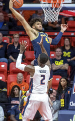 Michigan forward Isaiah Livers (4) goes up for a rebound over Illinois forward Kipper Nichols (2) during the first half of an NCAA college basketball game in Champaign, Ill., Thursday, Jan. 10, 2019. (AP Photo/Rick Danzl)