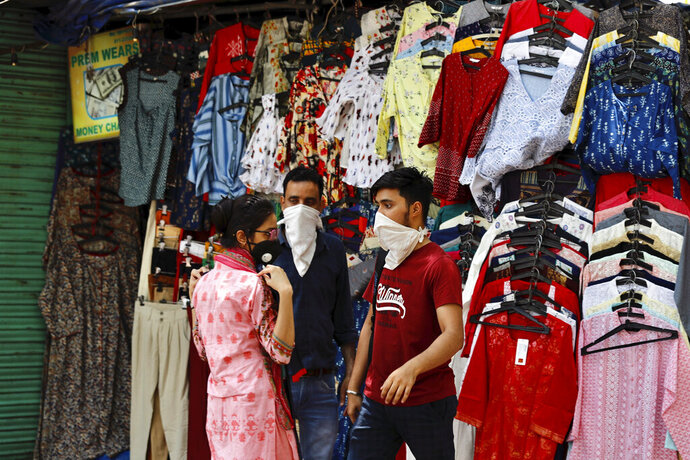 A woman shops for clothes at the Janpath market in New Delhi, India, Monday, June 1, 2020. More states opened up and crowds of commuters trickled onto the roads in many of India's cities on Monday as a three-phase plan to lift the nationwide coronavirus lockdown started despite an upward trend in new infections. (AP Photo/Manish Swarup)
