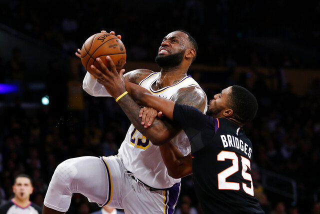 Los Angeles Lakers' LeBron James (23) is fouled by Phoenix Suns' Mikal Bridges (25) during the second half of an NBA basketball game Wednesday, Jan. 1, 2020, in Los Angeles. The Lakers won 117-107. (AP Photo/Ringo H.W. Chiu)