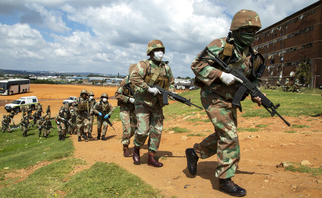 South African National Defence Forces take up positions outside the hostel in a densely populated Alexandra township east of Johannesburg, South Africa, Saturday, March 28, 2020. South Africa went into a nationwide lockdown for 21 days in an effort to control the spread of the COVID-19 coronavirus. The new coronavirus causes mild or moderate symptoms for most people, but for some, especially older adults and people with existing health problems, it can cause more severe illness or death. (AP Photo/Themba Hadebe)