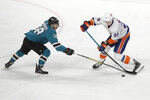 San Jose Sharks defenseman Mario Ferraro, left, reaches for the puck at the feet of New York Islanders center Brock Nelson during the third period of an NHL hockey game in San Jose, Calif., Saturday, Nov. 23, 2019. (AP Photo/Jeff Chiu)