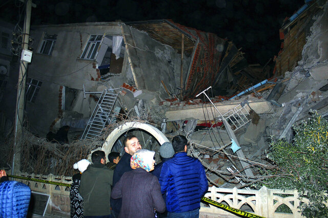 People look at a collapsed building after a 6.8 earthquake struck Elazig city centre in the eastern Turkey, Friday, Jan. 24, 2020. An earthquake with a preliminary magnitude of 6.8 rocked eastern Turkey on Friday, causing some buildings to collapse and killing at least four people, Turkish officials said. (IHA via AP)