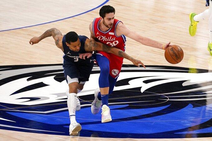 Dallas Mavericks guard Trey Burke (3) competes against Philadelphia 76ers guard Furkan Korkmaz (30) for control of a loose ball in the second half of an NBA basketball game in Dallas, Monday, April 12, 2021. (AP Photo/Tony Gutierrez)