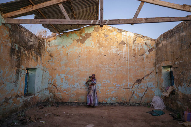 A Tigray woman who fled the conflict in Ethiopia's Tigray region holds her child inside of her temporary shelter at Umm Rakouba refugee camp in Qadarif, eastern Sudan, Monday, Dec. 7, 2020. (AP Photo/Nariman El-Mofty)