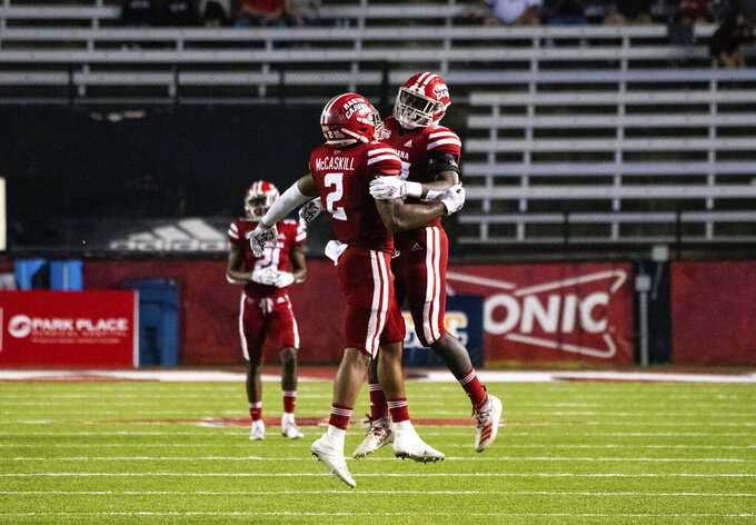 Louisiana-Lafayette linebackers Lorenzo McCaskill (2) and Tyler Guidry (33) celebrate a defensive stop during the first half of an NCAA football game against Coastal Carolina in Lafayette, La., Wednesday, Oct. 14, 2020. (AP Photo/Paul Kieu)