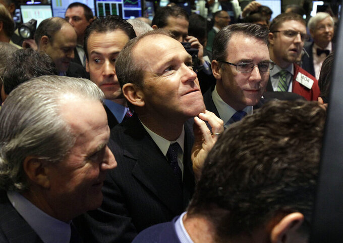 FILE - In this Jan. 26, 2011 file photo, Nielsen Company CEO David Calhoun, center, watches progress as he waits for the company's IPO to begin trading, on the floor of the New York Stock Exchange. Boeing CEO David Calhoun declined a salary and performance bonus for most of 2020 but still received stock benefits that pushed the estimated value of his compensation to more than $21 million, according to a regulatory filing Friday, March 5, 2021. (AP Photo/Richard Drew, File)