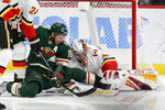 Calgary Flames goalie David Rittich (33) makes a stop on Minnesota Wild left wing Zach Parise (11) in the third period during an NHL hockey game Sunday, Jan. 5, 2020, in St. Paul, Minn. The Flames defeated the Wild 5-4 in the shoot out. (AP Photo/Andy Clayton-King)