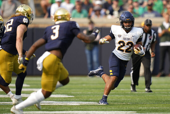 Toledo running back Bryant Koback (22) runs from Notre Dame safety Houston Griffith (3) in the second half of an NCAA college football game in South Bend, Ind., Saturday, Sept. 11, 2021. Notre Dame won 32-29. (AP Photo/AJ Mast)