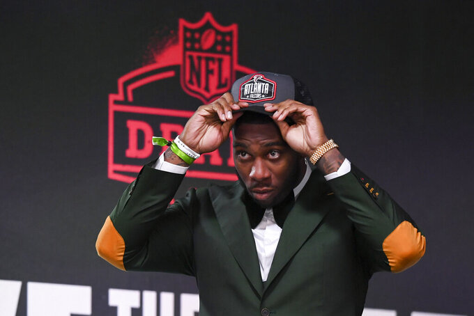 CORRECTS TO ATLANTA FALCONS NOT CINCINNATI BENGALS AND FOURTH PICK NOT FIFTH - Florida tight end Kyle Pitts puts on a team cap after he was chosen with the fourth overall pick by the Atlanta Falcons in the first round of the NFL football draft Thursday April 29, 2021, in Cleveland. (AP Photo/David Dermer)
