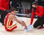 Atlanta Hawks guard Trae Young grabs his ankle after falling to the floor against the Milwaukee Bucks during the third quarter in Game 3 of the NBA Eastern Conference basketball finals, Sunday, June 27, 2021, in Atlanta. (Curtis Compton/Atlanta Journal-Constitution via AP)