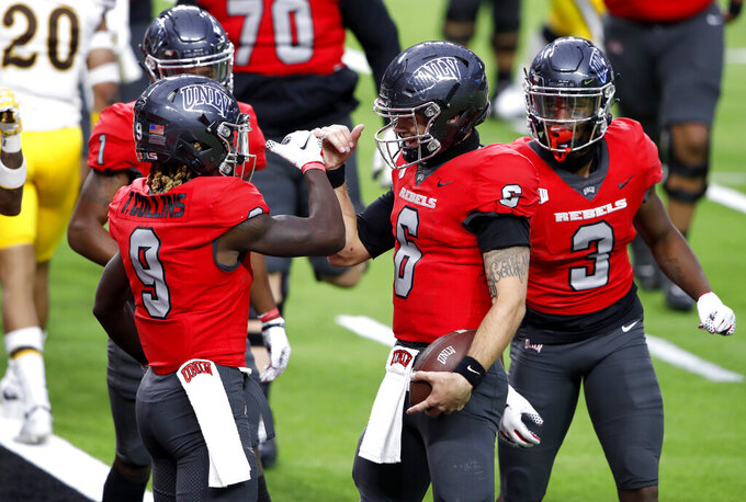 UNLV quarterback Max Gilliam, center, celebrates with teammates after scoring a touchdown against Wyoming during the first half of an NCAA college football game in Las Vegas on Friday, Nov. 27, 2020. (Steve Marcus/Las Vegas Sun via AP)
