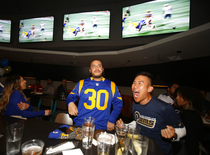 Frank Luh, right, and Luis Merida, second from right, react during a viewing party for the Super Bowl 53 football game between New England Patriots and the Los Angeles Rams in Los Angeles, Sunday, Feb. 3, 2019. (AP Photo/Ringo H.W. Chiu)