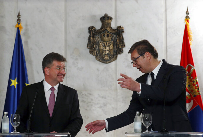 European Union envoy for the negotiations Miroslav Lajcak, left, listens Serbian President Aleksandar Vucic during a press conference after talks in Belgrade, Serbia, Monday, June 22, 2020. Europe and the United States are coordinating efforts toward urging Serbia and Kosovo to reach a deal. (AP Photo/Darko Vojinovic)