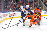 St. Louis Blues' Zach Sanford (12) works for the puck against Edmonton Oilers' Kris Russell (4) during the first period of an NHL hockey game Wednesday, Nov. 6, 2019, in Edmonton, Alberta. (Amber Bracken/The Canadian Press via AP)