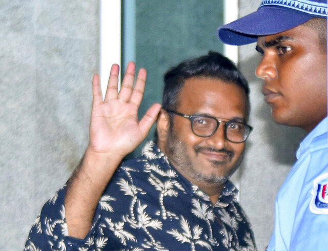 FILE- In this Aug. 5, 2019 file photo, Maldives' former Vice President Ahmed Adeeb, waves to journalists as he enters the police head quarters after being arrested in Male, Maldives. The former vice president of the Maldives has been sentenced to 20 years in prison after he pleaded guilty to money laundering and embezzlement under orders from the former president. (AP Photo, File)
