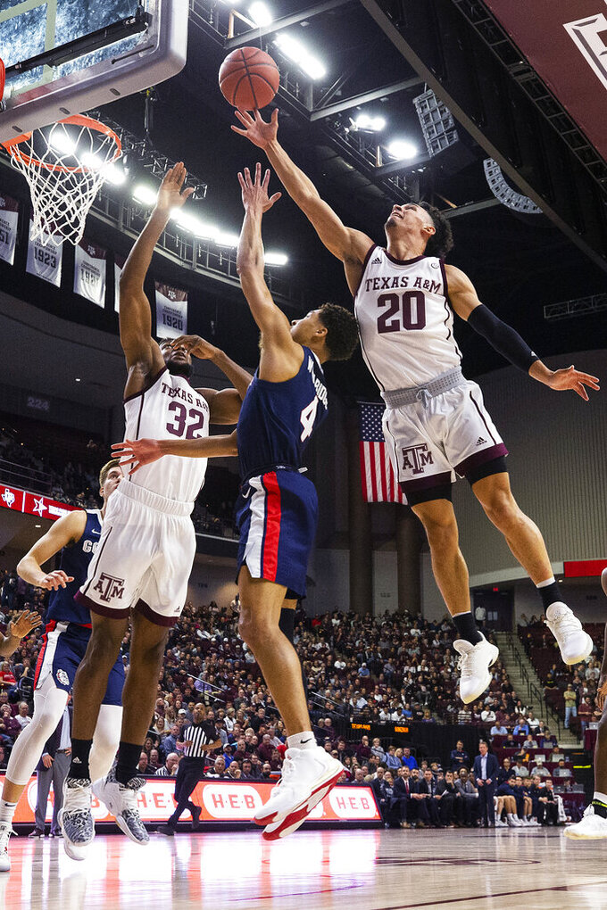 Texas A&M guard Andre Gordon (20) blocks a shot by Gonzaga guard Ryan Woolridge (4) during the first half of an NCAA college basketball game Friday, Nov. 15, 2019, in College Station, Texas. (AP Photo/Sam Craft)