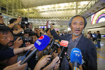 Chinese dissident writer Ma Jian shows his passport to media after arriving Hong Kong international airport, Friday, Nov. 9, 2018. Hong Kong on Friday permitted dissident writer Ma to enter to attend a literary festival, even after an arts venue in the city canceled his appearance. Ma, whose novels frequently satirize China's communist leaders, told reporters he experienced nothing unusual while passing through passport control and that organizers were still lining-up a place for him to speak.