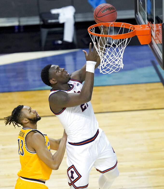 Illinois's Kofi Cockburn, right, scores past Drexel's Tim Perry Jr., during the first half of a first round NCAA college basketball tournament game Friday, March 19, 2021, at the Indiana Farmers Coliseum in Indianapolis .(AP Photo/Charles Rex Arbogast)