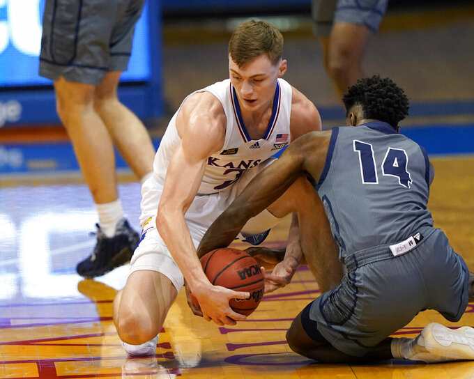 Kansas guard Christian Braun (2) and Washburn guard Tyler Nelson (14) compete for a loose ball during the first half of an NCAA college basketball game in Lawrence, Kan., Thursday, Dec. 3, 2020. (AP Photo/Orlin Wagner)
