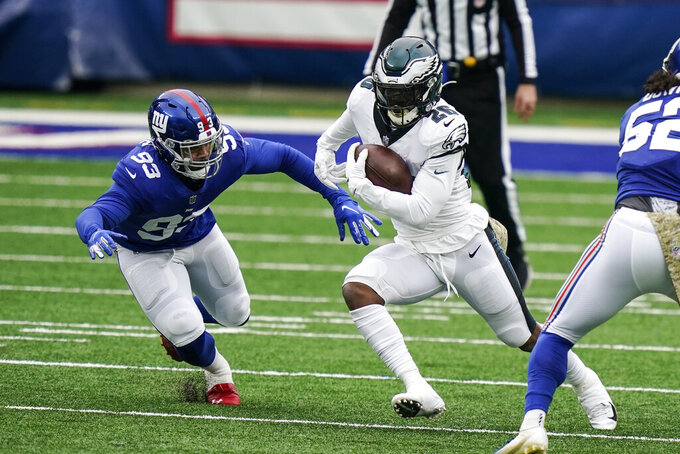 Philadelphia Eagles' Miles Sanders (26) rushes past New York Giants' Trent Harris (93) during the first half of an NFL football game Sunday, Nov. 15, 2020, in East Rutherford, N.J. (AP Photo/Corey Sipkin)
