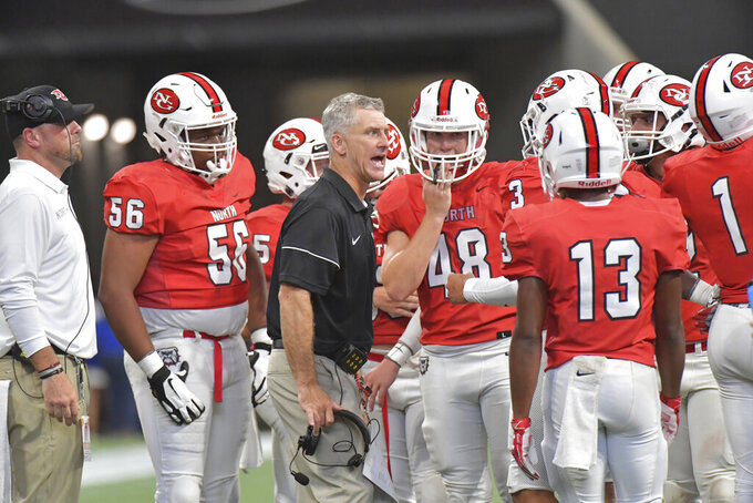 In this Aug. 24, 2019 photo, North Gwinnett head coach Bill Stewart instructs his team in the second half of the Corky Kell Classic high school football game against Colquitt County at Mercedes-Benz Stadium in Atlanta. Georgia has become the clear No. 4 state behind Texas, Florida and California for producing major college football players. (Hyosub Shin/Atlanta Journal-Constitution via AP)