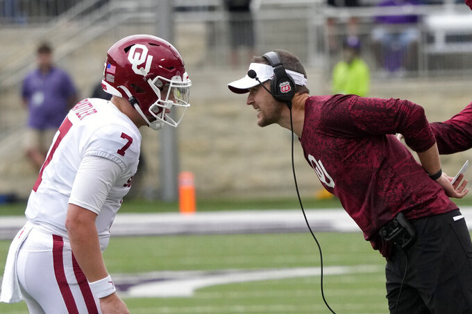Oklahoma head coach Lincoln Riley, right, talks with quarterback Spencer Rattler (7) during the first half of an NCAA college football game against Kansas State in Manhattan, Kan., Saturday, Oct. 2 2021. (AP Photo/Orlin Wagner)