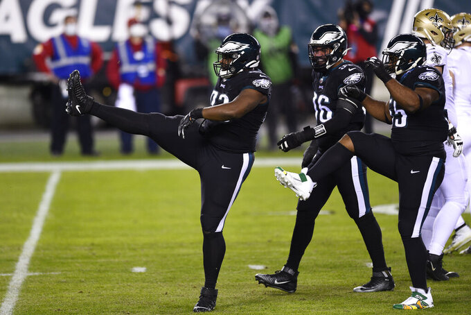 Philadelphia Eagles' Javon Hargrave, left, reacts after sacking New Orleans Saints' Taysom Hill during the first half of an NFL football game, Sunday, Dec. 13, 2020, in Philadelphia. (AP Photo/Derik Hamilton)