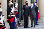 French President Emmanuel Macron, right, and Libyan Prime Minister Abdulhamid Dbeibeh wave before a meeting at the Elysee Palace in Paris, Tuesday, June 1, 2021. (AP Photo/Francois Mori)