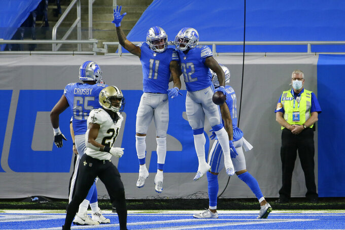 Detroit Lions running back D'Andre Swift (32) celebrates his 7-yard pass for a touchdown with teammate Marvin Jones (11) during the first half of an NFL football game against the New Orleans Saints, Sunday, Oct. 4, 2020, in Detroit. (AP Photo/Duane Burleson)