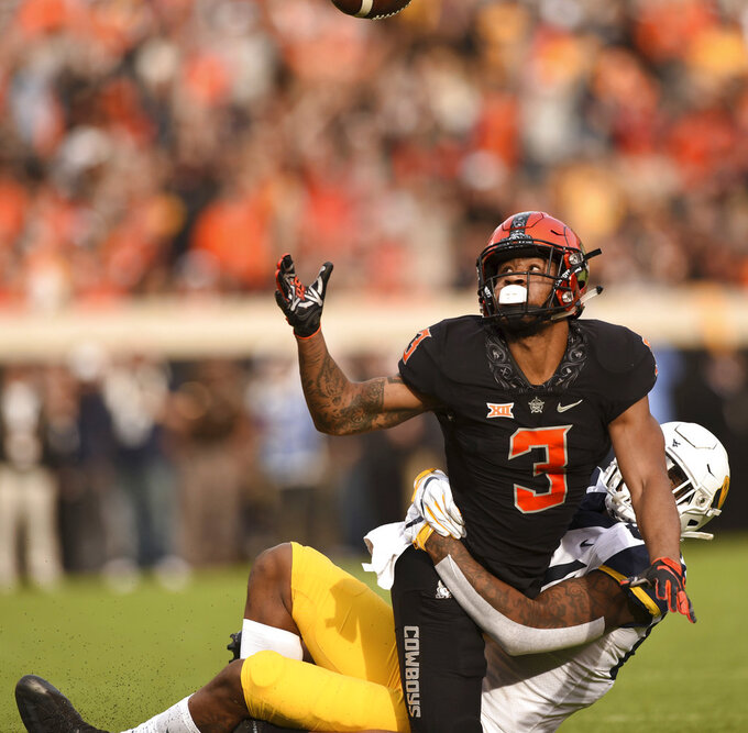 Oklahoma State safety Kenneth Edison-McGruder (3) reaches for the ball while being wrapped up by West Virginia wide receiver Marcus Simms, the intended receiver, during an NCAA college football game in Stillwater, Okla., Saturday, Nov. 17, 2018. (AP Photo/Brody Schmidt)