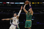 Boston Celtics' Jayson Tatum (0) makes a 3-point basket over Los Angeles Lakers' Danny Green (14) during the first half of an NBA basketball game Sunday, Feb. 23, 2020, in Los Angeles. (AP Photo/Marcio Jose Sanchez)